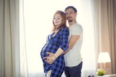 Mannen och en gravid ung kvinna väntar på ett barn hemmastatt b fotografering för bildbyråer