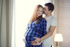 Mannen och en gravid ung kvinna väntar på ett barn hemmastatt b arkivbilder