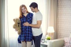 Mannen och en gravid ung kvinna väntar på ett barn hemmastatt b royaltyfri foto