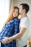 Mannen och en gravid ung kvinna väntar på ett barn hemmastatt b arkivfoton