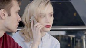 Mannen och en härlig kvinna gör en beställning vid telefonen till leveransavdelningen arkivfilmer
