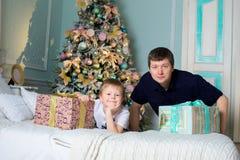 Mannen och ett barn mottog gåvor Fadern och sonen nytt år royaltyfri fotografi