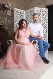 Mannen och gravida kvinnan i rosa färger poserar på den barocka fåtöljen Royaltyfri Foto