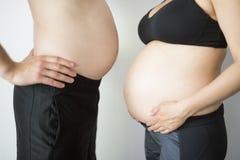 Mannen och gravida kvinnan visar deras bukar, sidosikt Arkivfoton