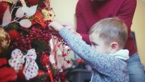 Mannen och hans son dekorerar julgranen arkivfilmer