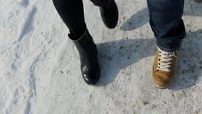 Mannen och kvinnan är den jämbördiga graden på en snöig väg i den varma skon stock video