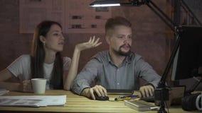 Mannen och kvinnan arbetar sent på natten, kontorsarbete på datoren Diskussion om arbete arkivfilmer