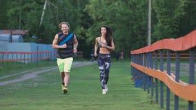 Mannen och kvinnan begår en jogga De är unga, och attraktivt, meddela med de positivt arkivfilmer