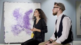 Mannen och kvinnan besöker modern konstgallerit och lyssnande musik vid hörlurar lager videofilmer