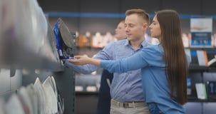 Mannen och kvinnan för familjpar väljer den härliga nytt järn shoppar in lager videofilmer