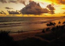 Mannen och kvinnan fotograferas i havet på solnedgången royaltyfri foto