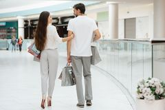 Mannen och kvinnan går till ett annat lager i shoppinggalleria Paret är lyckligt fotografering för bildbyråer