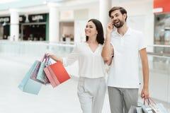 Mannen och kvinnan går till ett annat lager i shoppinggalleria Mannen talar på telefonen arkivfoton