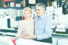Mannen och kvinnan 48-56 gamla år besöker shoppar av hushållet app Arkivfoton
