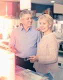 Mannen och kvinnan 49-54 gamla år besöker shoppar av hushållet app Arkivbild