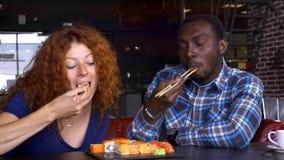 Mannen och kvinnan i ett kafé äter sushi och meddelar lager videofilmer