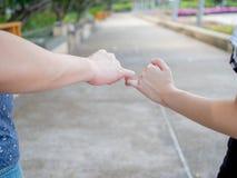 Mannen och kvinnan i förhållandekorsning lillfinger fingrar som lovat Royaltyfria Foton