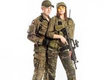 Mannen och kvinnan i soldat` s passar på vit bakgrund Arkivfoton