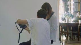Mannen och kvinnan i vita skjortor gör bilder av fannypacke under photosession stock video
