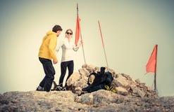 Mannen och kvinnan kopplar ihop handelsresande på bergtoppmöte royaltyfri bild