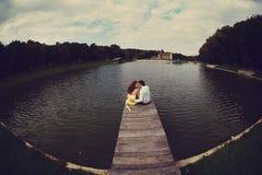 Mannen och kvinnan kramar sammanträde på bron på sjön arkivfoto