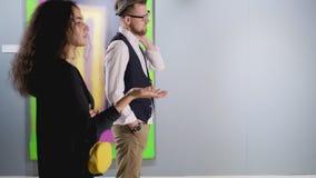 Mannen och kvinnan ogillar den abstrakta moderna bilden i gallerikorridoren som bort går arkivfilmer