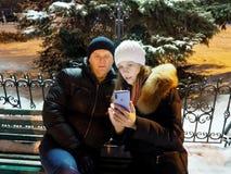 Mannen och kvinnan på en bänk i vinter parkerar i aftonen royaltyfria foton