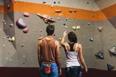 Mannen och kvinnan på ett inomhus vaggar klättringidrottshall arkivfoto