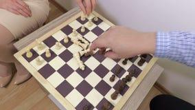Mannen och kvinnan satte schackstycken på schackbrädet stock video