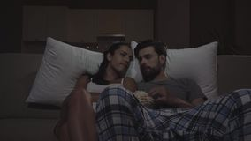 Mannen och kvinnan sitter i mörker på soffan och hållande ögonen på film De äter popcorn Flickastarter till att falla sovande De  arkivfilmer