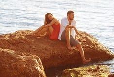 Mannen och kvinnan sitter på en sorgsten royaltyfri bild