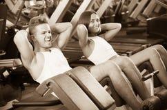 Mannen och kvinnan som gör abs, övar i idrottshall Arkivfoton