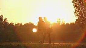 Mannen och kvinnan som har det romantiska datumet i härligt, parkerar och att gå i solnedgångstrålar lager videofilmer