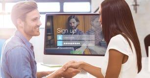 Mannen och kvinnan som skakar händer med, undertecknar upp sidan på bildskärm i bakgrund royaltyfria foton