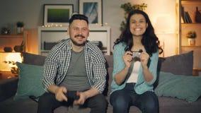 Mannen och kvinnan som spelar videospelet i lägenhet, den lyckliga flickan, segrar stock video