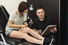 Mannen och kvinnan som väljer tatueringen, planlägger i studio fotografering för bildbyråer
