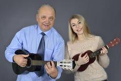 Mannen och kvinnan spelar gitarren Royaltyfri Fotografi