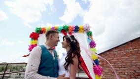 Mannen och kvinnan, ungdomar, lyckliga gifta vuxna par som står near bröllop, välva sig stock video