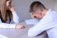 Mannen och kvinnan var de mycket trötta från arbete och sammanträde på Tabl Royaltyfri Bild