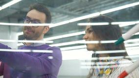 Mannen och kvinnliga teknikerer använder ett plast- bräde och har en diskussion stock video