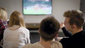 Mannen och kvinnliga ungdomarsitter på soffan i lägenhet och hållande ögonen på fotboll vid stor tv stock video
