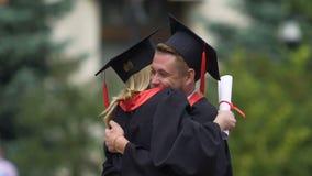 Mannen och kvinnlign avlägger examen i akademiska lock som kramar, vänner som är ledsna att säga farväl stock video