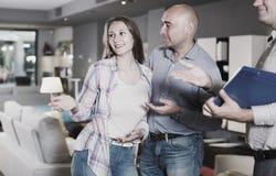 Mannen och kvinnlign konsulterar med säljaren för att välja den nya soffan Royaltyfri Fotografi