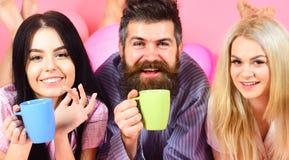 Mannen och kvinnor, vänner på att le framsidor lägger, rosa bakgrund Förälskat drinkkaffe för vänner i säng Man och kvinnor in Royaltyfria Foton