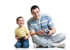 Mannen och pojken spelar med en playstation tillsammans Royaltyfria Bilder