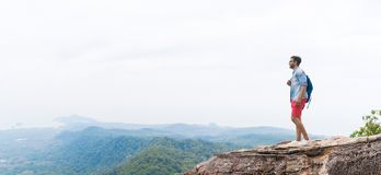Mannen på bergmaximumet som lyfter händer med ryggsäckar, tycker om landskapfrihetsbegreppet, unga Guy Tourist royaltyfri bild