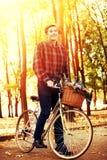 Mannen på cykeln med blommor som korgen rider sommar, parkerar Royaltyfri Fotografi