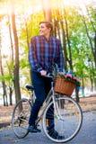Mannen på cykeln med blommor som korgen rider sommar, parkerar Fotografering för Bildbyråer