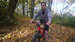 Mannen på cykeln rider förbi i skogman på cykelritter förbi i skogultrarapid stock video