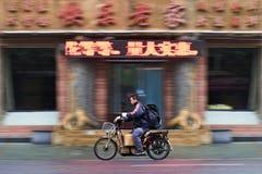 Mannen på en elektrisk cykel passerar en restaurang, Dalian, Kina Arkivbild